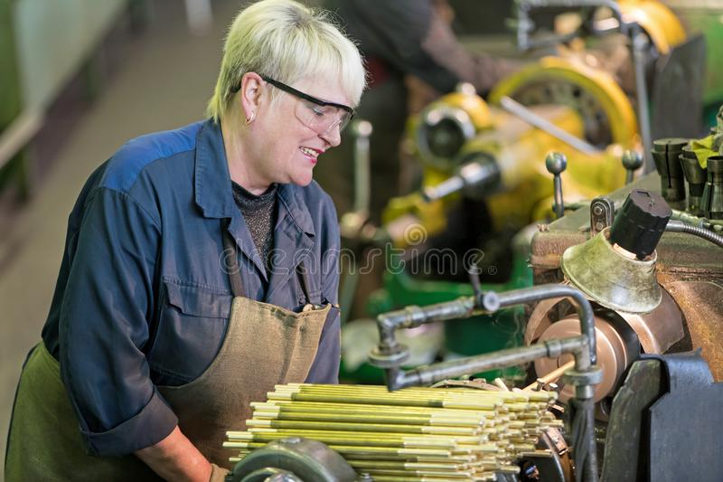 Factory woman turner working on workshop lathe machine royalty free stock images