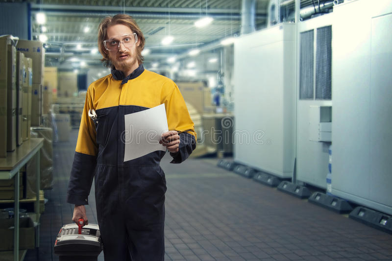 Factory worker. Young handsome worker in uniform standing and holding in one hand paper, in other- tool box. Looking straight to the camera. Over factory royalty free stock images