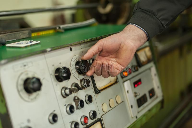 Factory worker adjusts the control panel of industry machine royalty free stock photography
