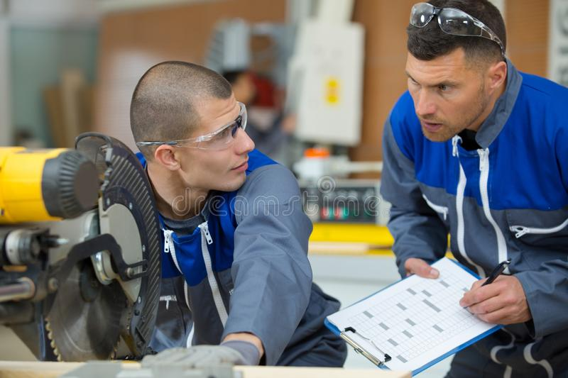 Factory worker and apprentice marking workpiece stock images