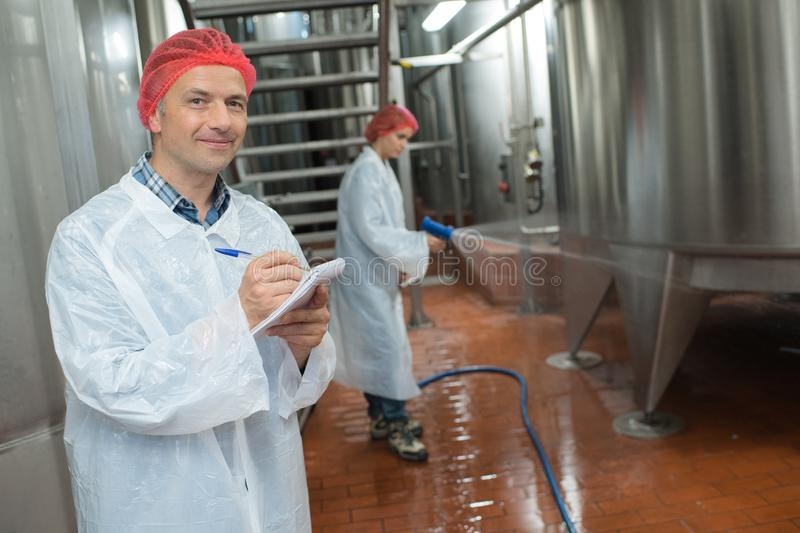 Factory worker cleaning floor. Factory royalty free stock image