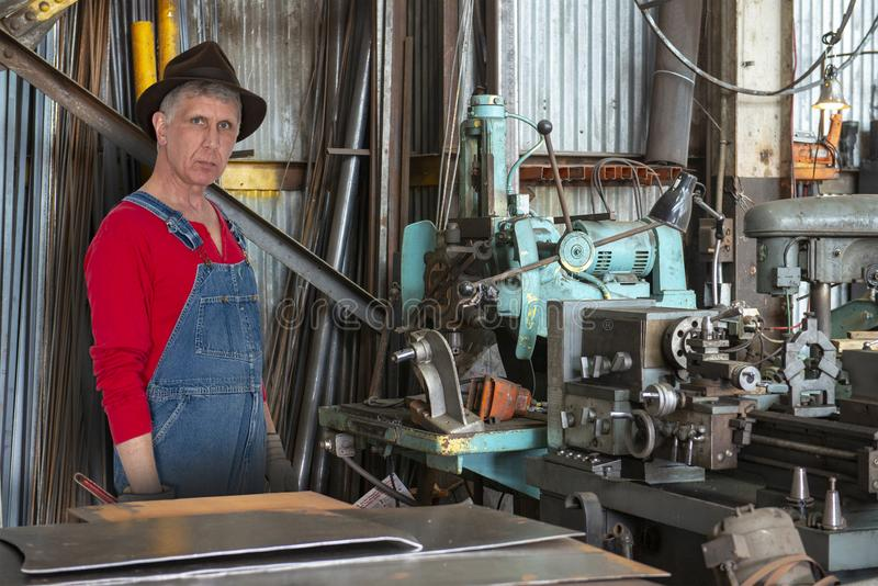 Factory Worker, Machinist, Machines, Industrial Job. A factory worker man is a machinist in an industrial manufacturing facility. The skilled laborer works hard stock photography