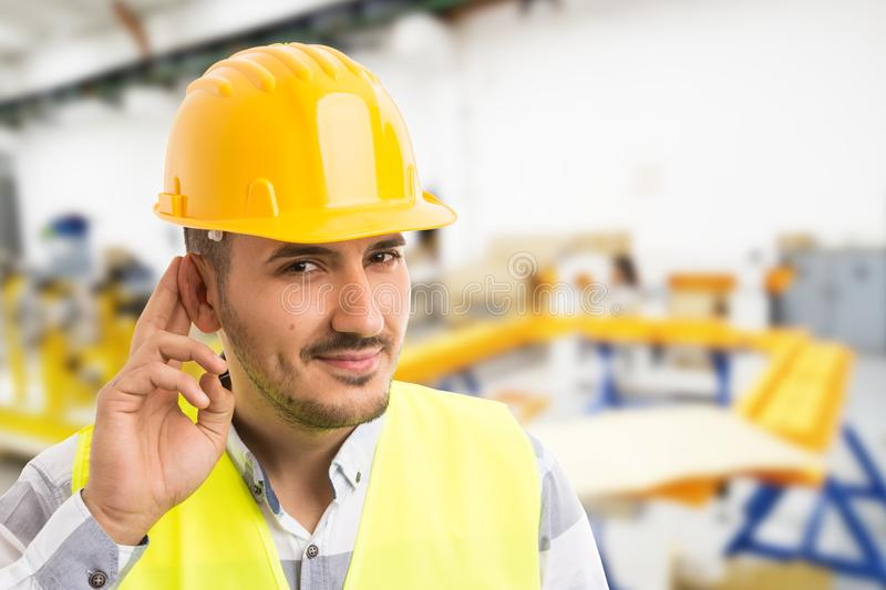 Factory worker making can`t hear you because of noise gesture. By leaning and touching his ear. He is also a repairman technician or electrician stock photography