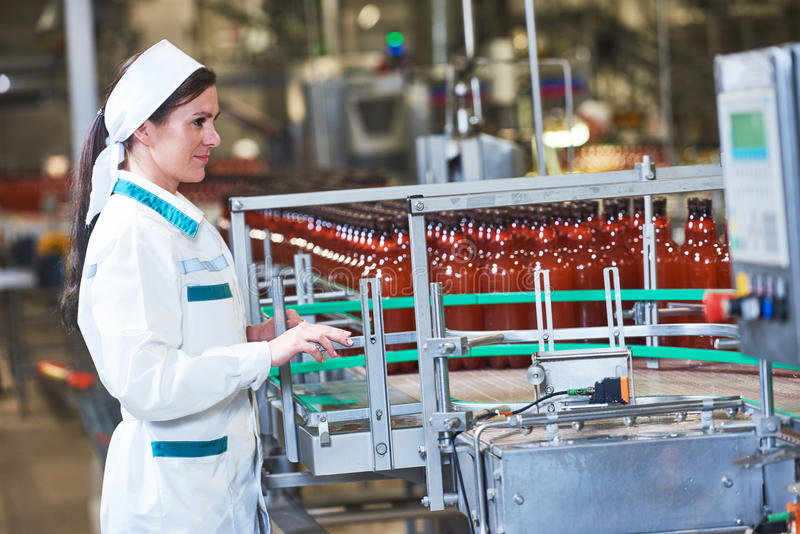 Factory worker operating conveyor with beer beverage bottles mov stock photography