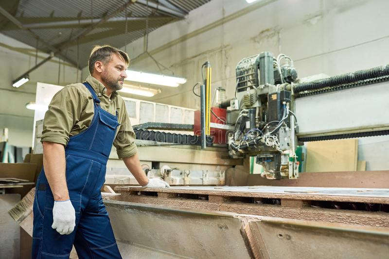 Factory Worker using Cutting Machine stock image