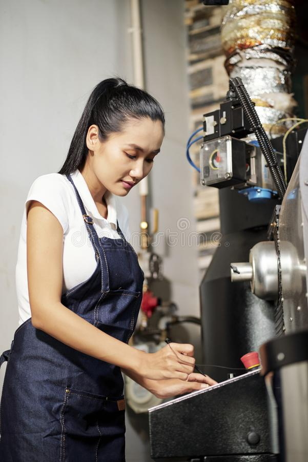 Factory worker working with machine. Female factory worker in apron working on computer machinery equipment and setting the program on it before work of stock image