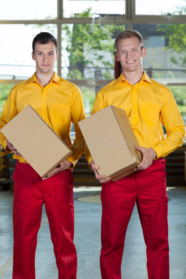 Factory workers with boxes. Vertical view of factory workers with boxes stock photography