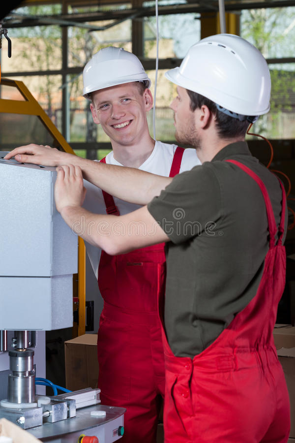 Factory workers checking the machinery. Cheerful factory workers checking the machinery at workshop royalty free stock photo