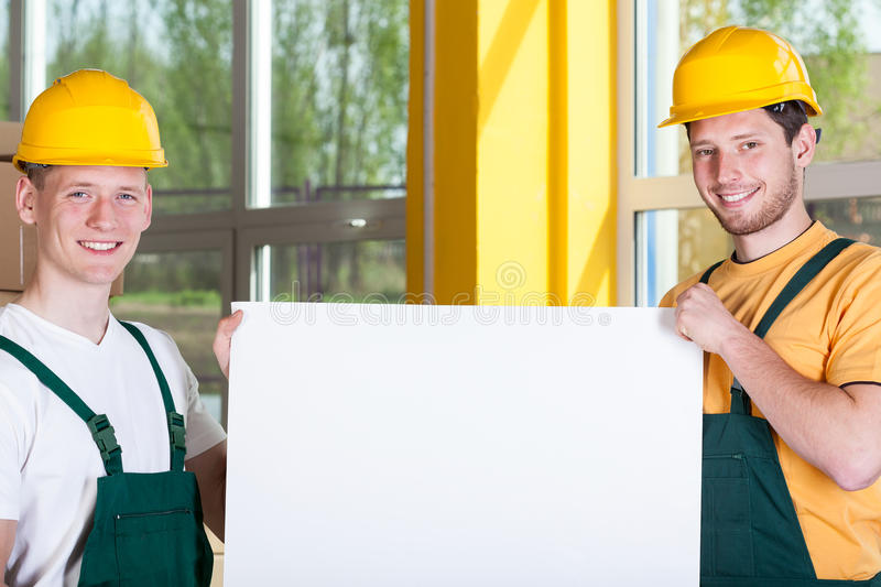 Factory workers holding a white board. Factory workers holding a blank white board, horizontal stock photos