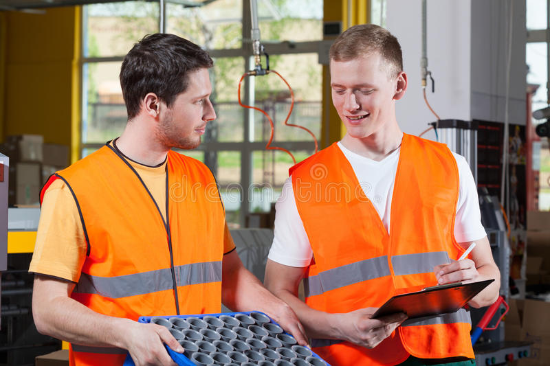 Factory workers in orange protective vest. During work stock photos