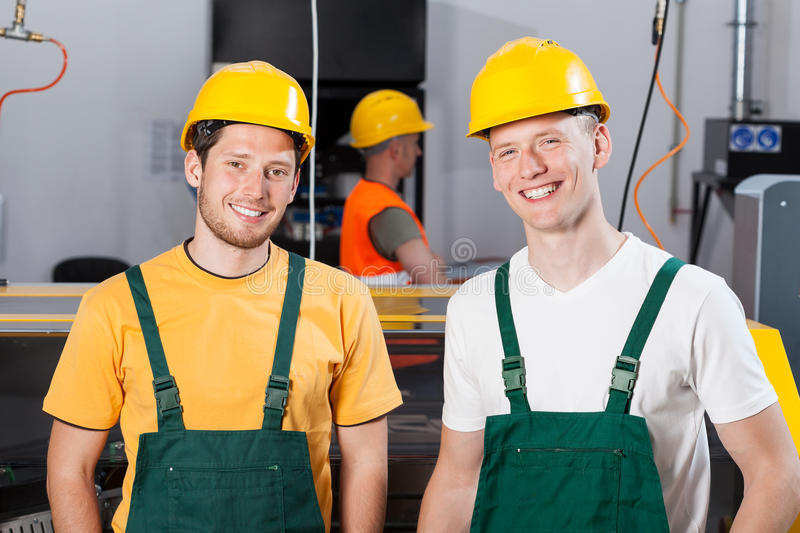 Factory workers at production area. Portrait of a smiling factory workers at production area royalty free stock images