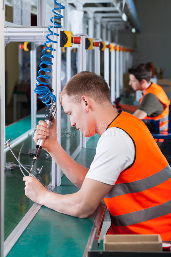 Factory workers on the production line. Using pneumatic screwdriver royalty free stock photos