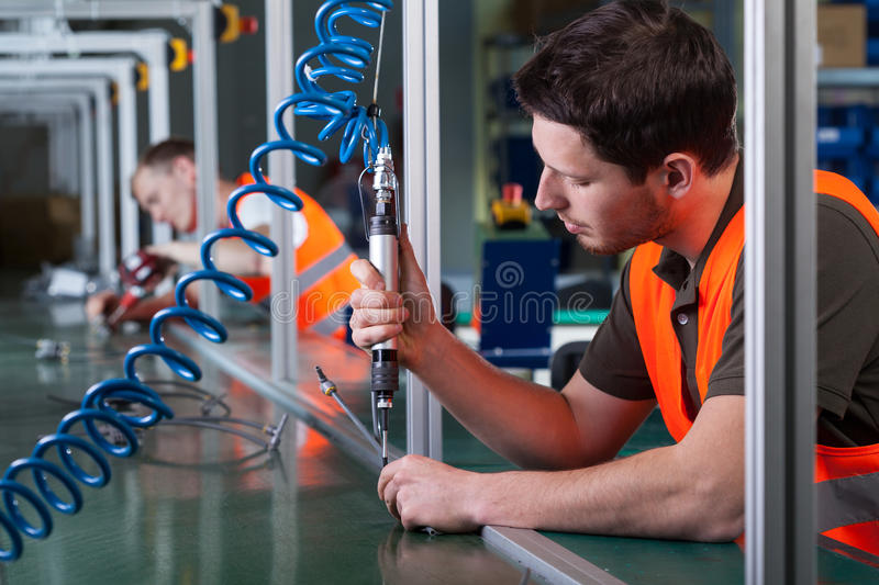 Factory workers and production process. Horizontal view of factory workers and production process stock photo