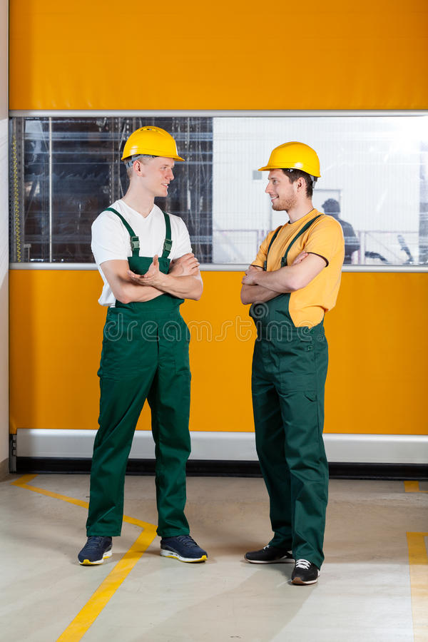 Factory workers standing with arms crossed. Vertical view of a factory workers standing with arms crossed and talking royalty free stock photography