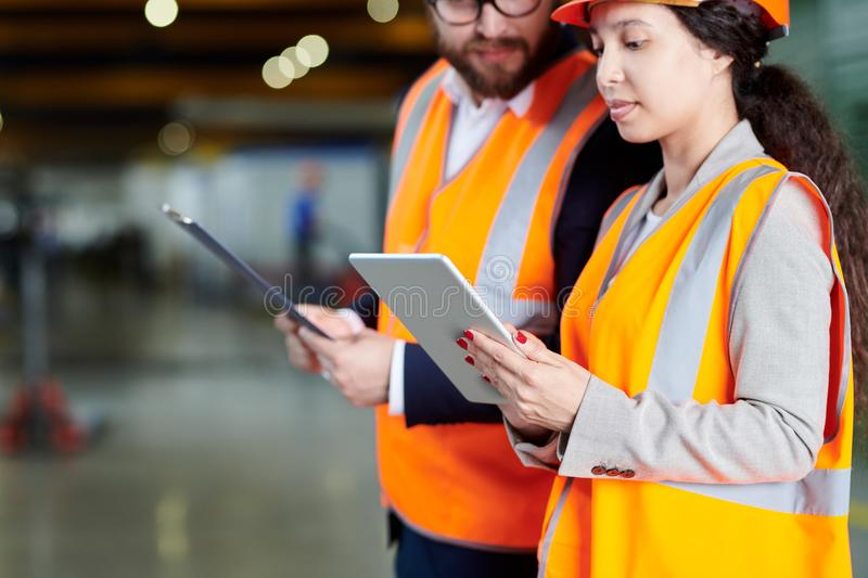 Factory Workers Using Digital Tablet. Mid section portrait of female factory worker using digital tablet while discussing production with foreman in workshop royalty free stock photos