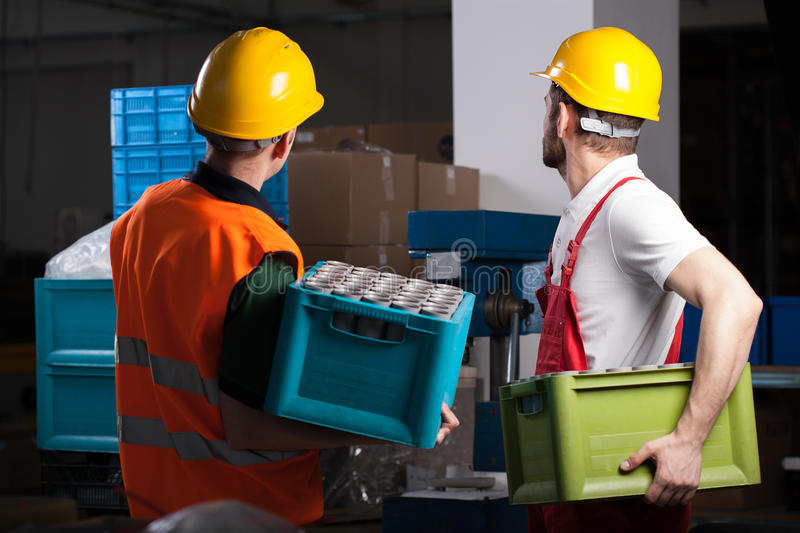Factory workers during work. Two factory workers holding boxes with equipment during work royalty free stock image