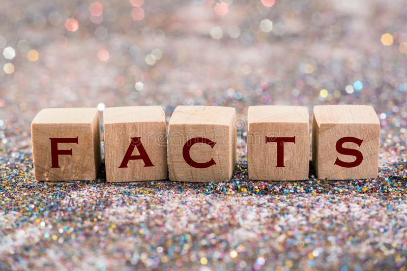 Facts word. Wood Cubes Facts word on glitter background royalty free stock photo