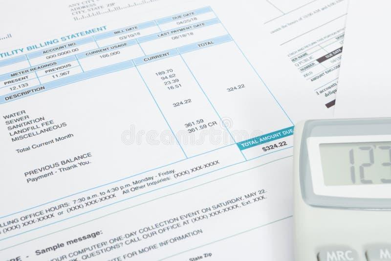 Factura de servicios públicos y calculadora sin pagar sobre ella - tiro ascendente cercano del estudio imágenes de archivo libres de regalías
