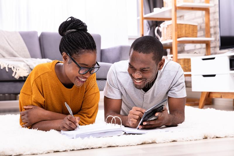 Facture calculatrice de couples africains avec la calculatrice photo libre de droits