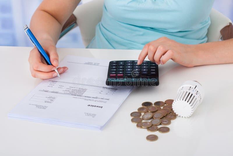 Facture calculatrice de femme par des pièces de monnaie et thermostat au bureau photos stock