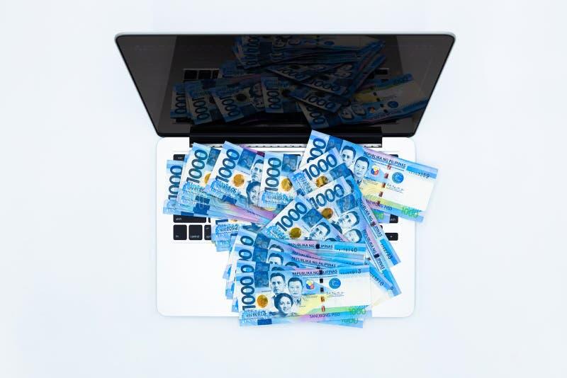 Facture de peso philippin avec l'ordinateur portable, devise d'argent de Philippines, factures d'argent philippines fond, concept photo libre de droits