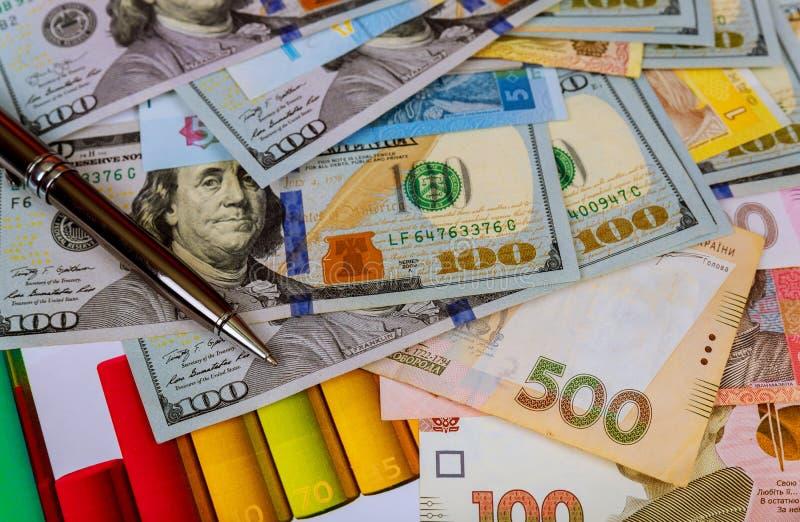 Factures d'argent ukrainiennes de hryvnia et cent dollars américains photographie stock