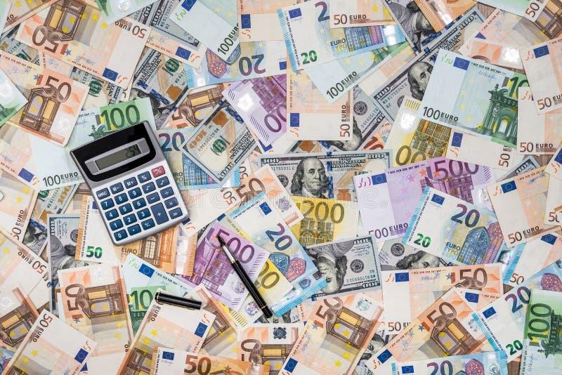 Factures du dollar et d'euro de la pile OD avec la calculatrice image libre de droits