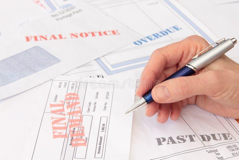 Factures et factures en retard avec le crayon lecteur à disposition photos stock