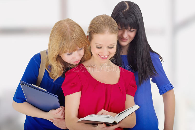Faculdade agradável de três meninas que discute o livro fotos de stock royalty free