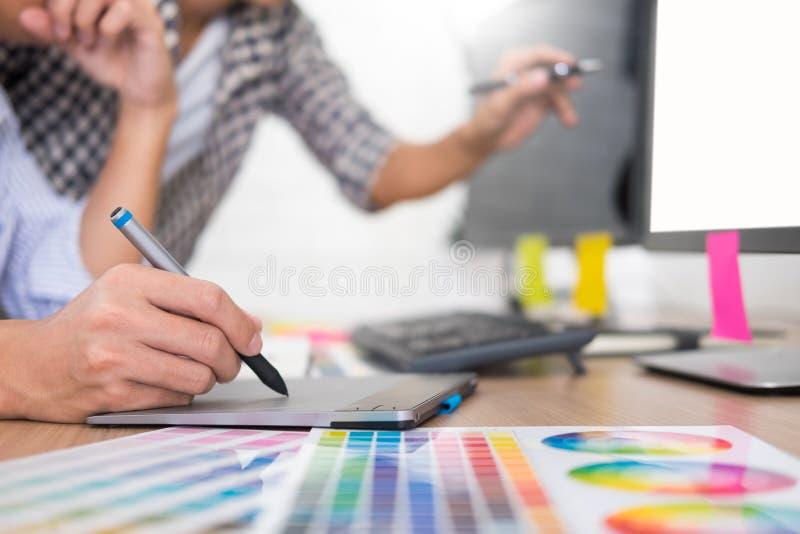Faculdade criadora criativa gráfica do desenhista que trabalha junto colorir usando a tabuleta de gráficos e um estilete na mesa  fotografia de stock royalty free