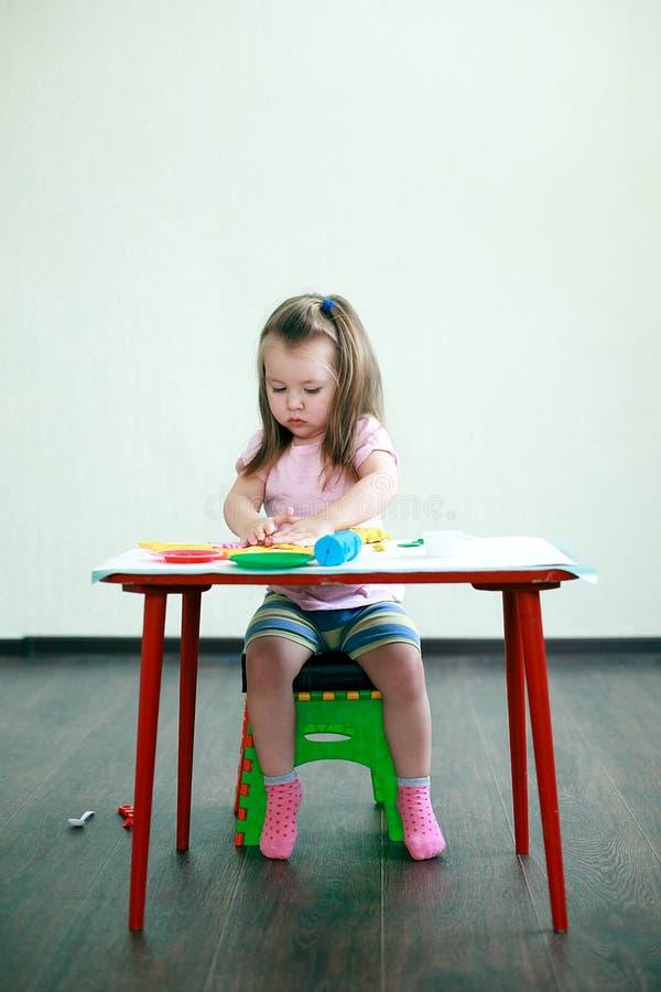 Faculdade criadora das crianças A criança esculpe da argila 2 anos pequenos bonitos dos moldes da menina do plasticine na tabela  fotografia de stock royalty free