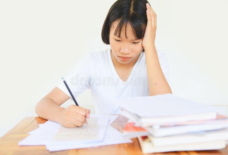 A faculdade fêmea nova do esforço/educação do exame na classe que toma notas e que usa um lápis que senta-se aprendendo o conceit fotografia de stock royalty free