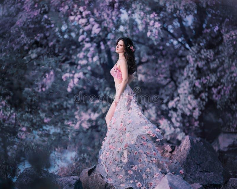 A fada da mola está no fundo de uma florescência, árvore rosado Veste um vestido cor-de-rosa com flores que vibre fotos de stock royalty free