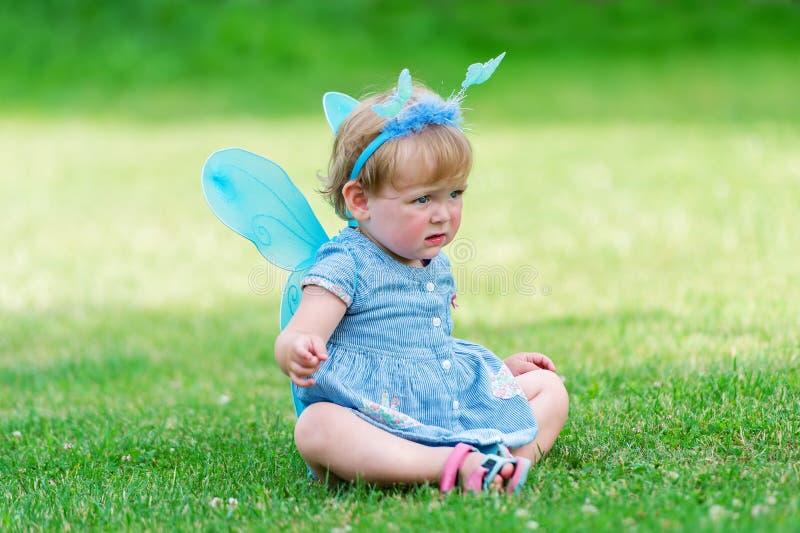 A fada pequena em um vestido azul senta-se no gramado fotografia de stock royalty free