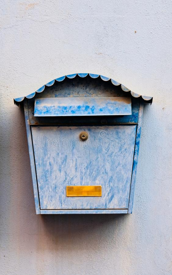 Faded Blue Mail Box on Pale Blue Wall stock photo