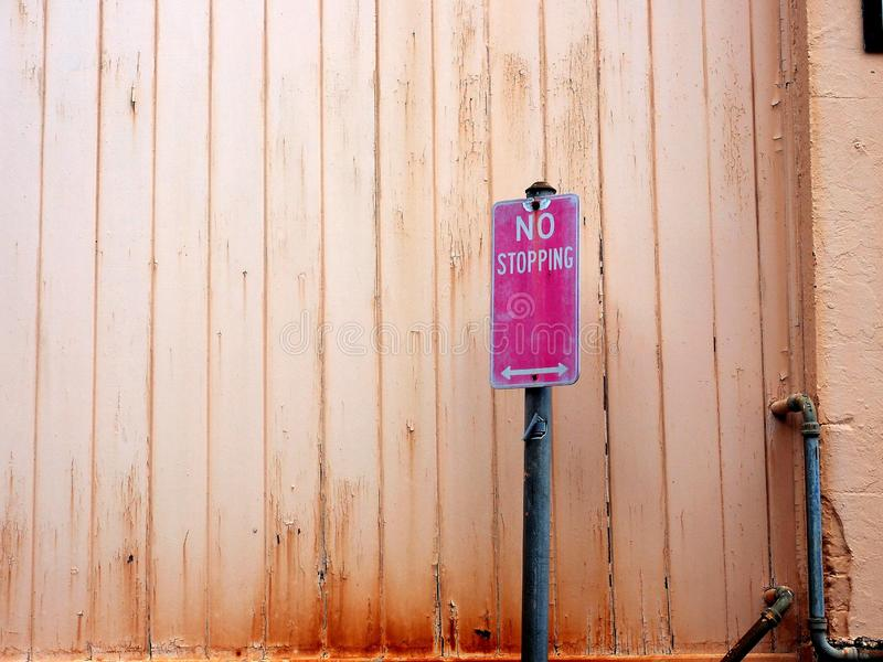 Faded No Stopping Traffic Sign and pale Wood Wall. A faded red and white no stopping traffic control sign beside a pale salmon coloured wooden house wall with royalty free stock photo