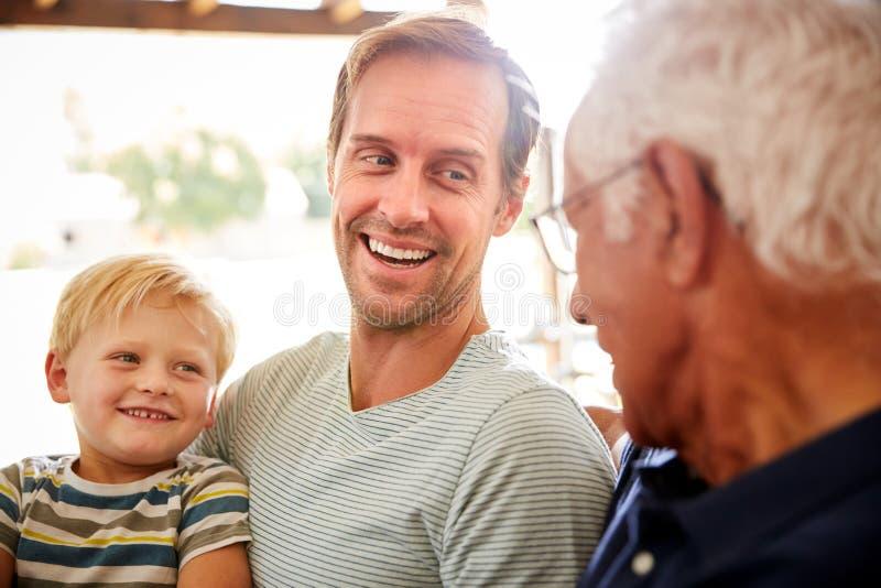 Fader With Adult Son och sonson som kopplar av på Sofa And Talking At Home royaltyfria foton