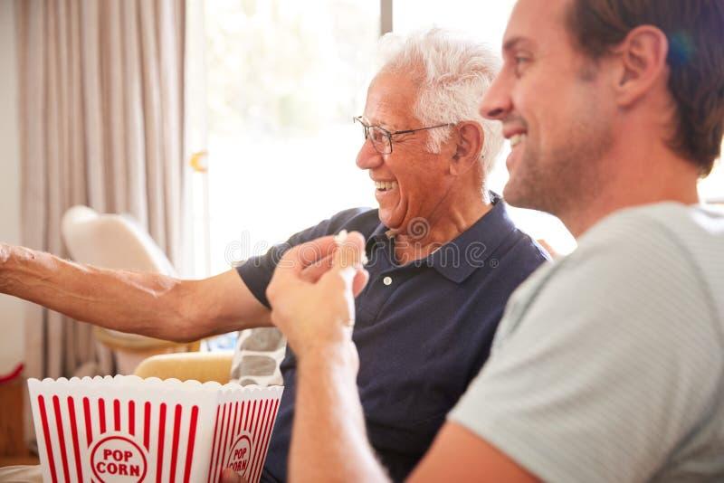 Fader With Adult Son som äter hållande ögonen på film för popcorn på Sofa At Home Together fotografering för bildbyråer