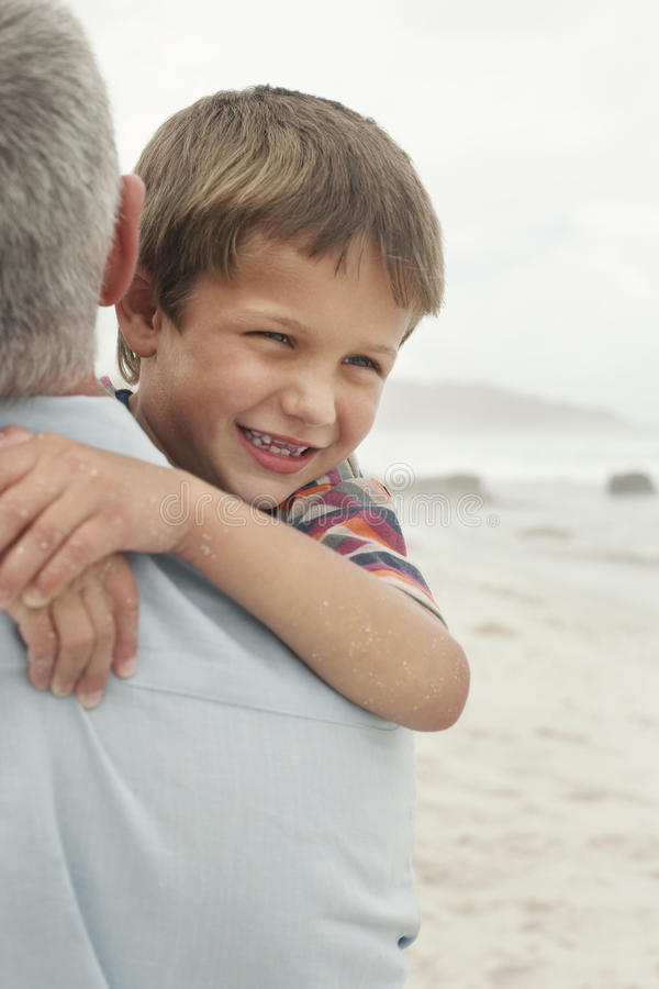 Fader Carrying Happy Boy på stranden royaltyfri fotografi