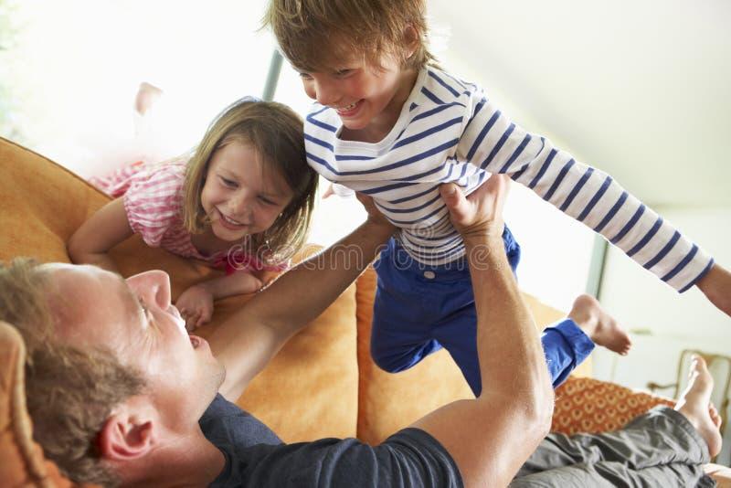 Fader And Children Lying på Sofa At Home royaltyfri foto