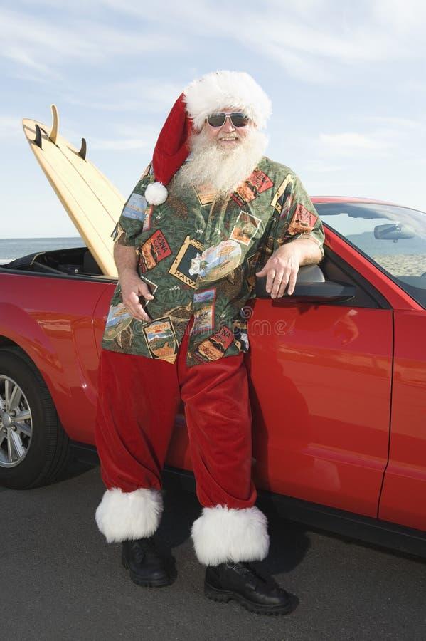 Fader Christmas By Convertible med surfingbrädan arkivbild