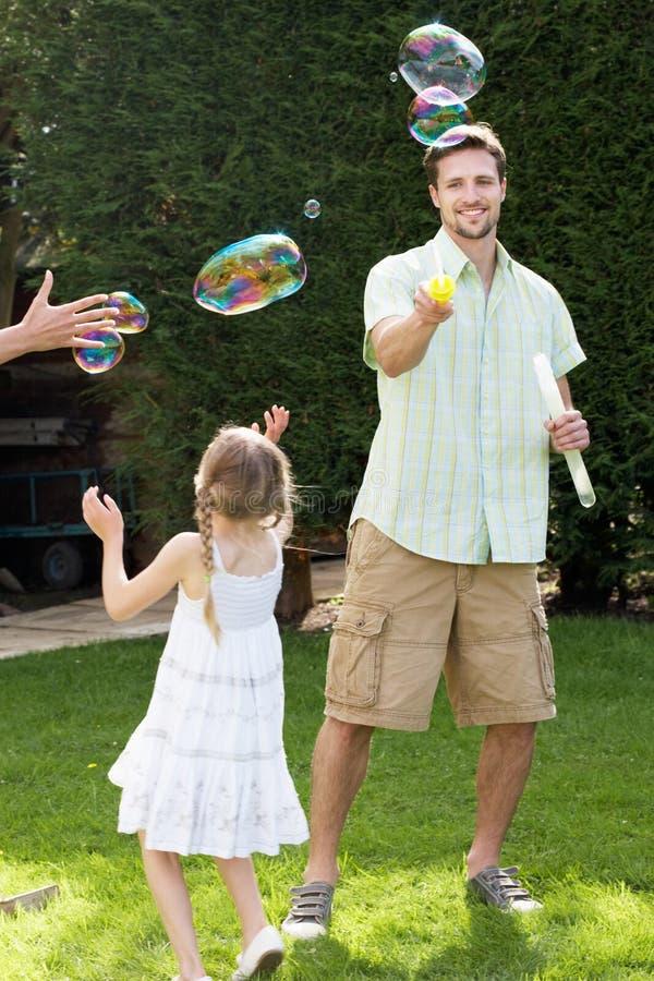 Fader And Daughter Playing med bubblor i trädgård arkivbild