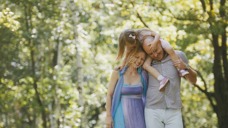 Fader - djärv man, moder - blond härlig kvinna och liten flicka - gå i parkera på den soliga dagen royaltyfria foton