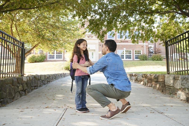 Fader Dropping Off Daughter i Front Of School Gates royaltyfri fotografi