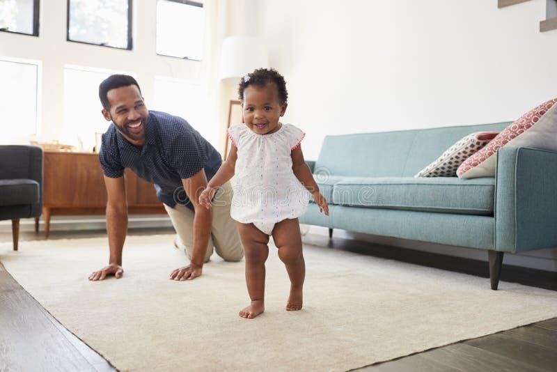 Fader Encouraging Baby Daughter som hemma tar första steg royaltyfria foton