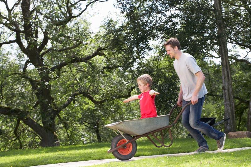 Fader Giving Son Ride i skottkärra royaltyfri foto