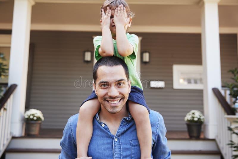 Fader Giving Son Ride på skuldrayttersidahus royaltyfri fotografi