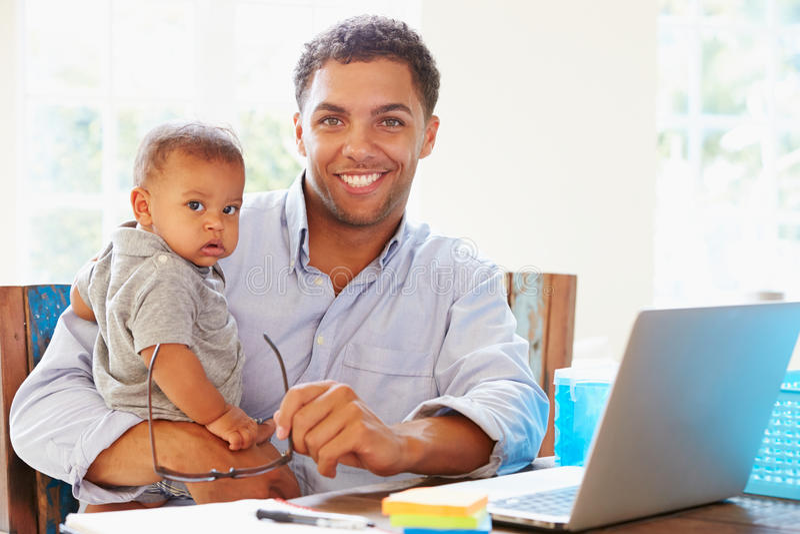 Fader hemmastadda With Baby Working i regeringsställning royaltyfri bild