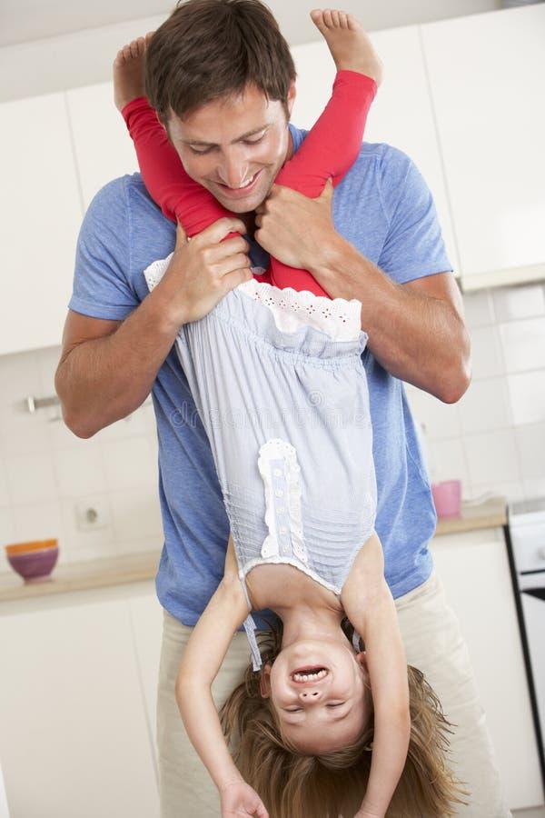Fader hemmastadda Holding Daughter Upside ner royaltyfri fotografi
