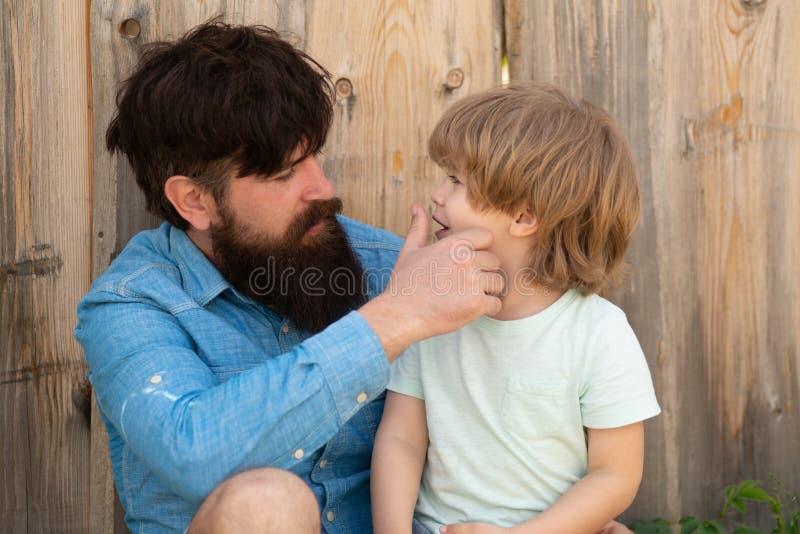 Fader kontrollerar tänderna på sin son Vård för barntänder Pappa och pojken sitter nära stängslet Caring far Familj royaltyfria foton